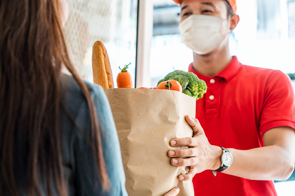 Man with face mask delivering groceries